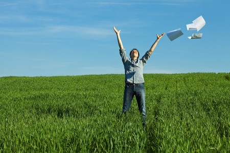 getting away from it all: man throws the paper in the field Stock Photo