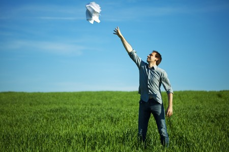 man throws the paper in the field photo