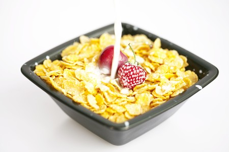 bowl of cornflakes milk  cherry  and strawberry  isolated on white photo