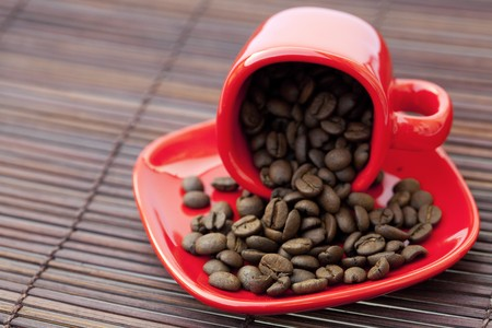 cup and saucer and coffee beans on a bamboo mat photo