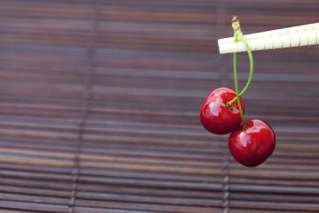 cherry and chopsticks on bamboo mat photo