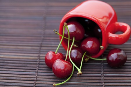cherry  and cup  on bamboo mat photo