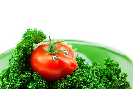 tomato with eyes on a plate isolated on white photo