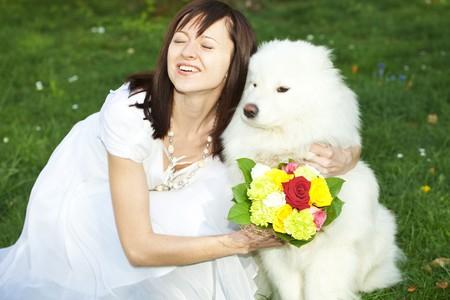 Bride with dog Samoyed sitting on the grass photo