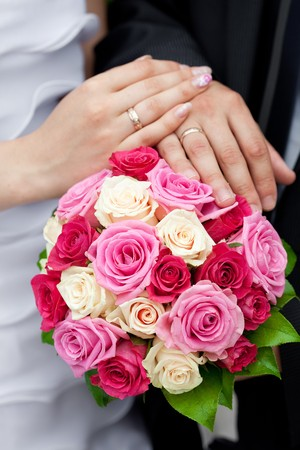wedding vows: the hands of the bride and groom lying on the bridal bouquet