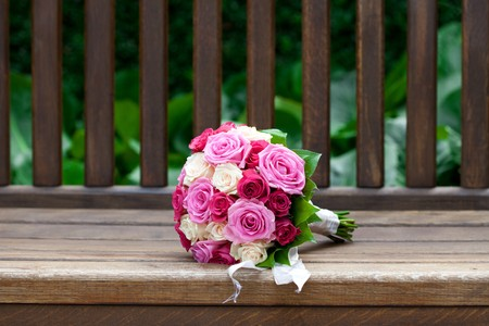 beautiful bridal bouquet lying on the wooden benches Stock Photo