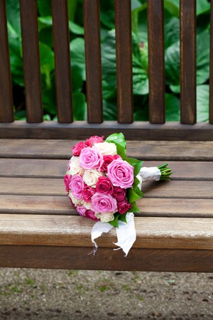 beautiful bridal bouquet lying on the wooden benches photo