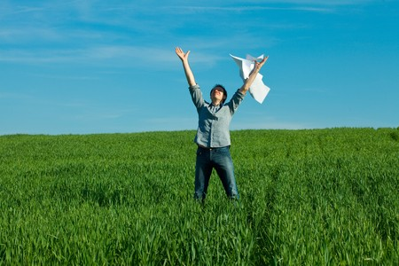young man throwing a paper in the green field Stock Photo - 7778257