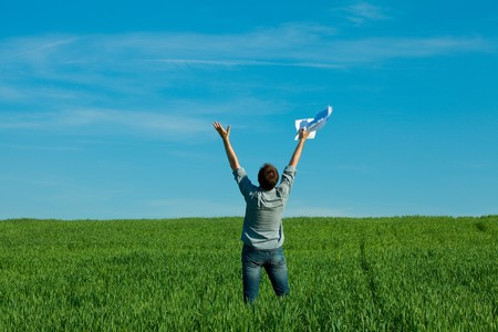 young man throwing a paper in the green field Stock Photo - 7778238