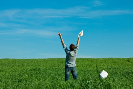 young man throwing a paper in the green field Stock Photo - 7778237