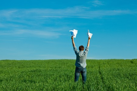 young man throwing a paper in the green field photo
