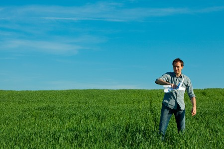 young man throwing a paper in the green field Stock Photo - 7778235