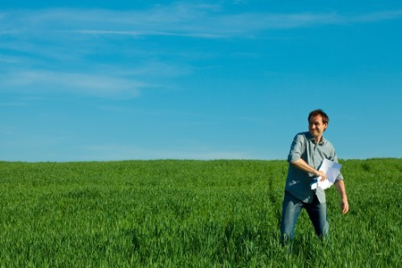 young man throwing a paper in the green field Stock Photo - 7778232