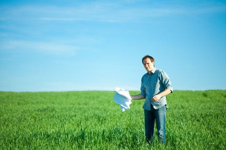 young man throwing a paper in the green field Stock Photo - 7778185