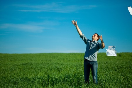 young man throwing a paper in the green field Stock Photo - 7778189