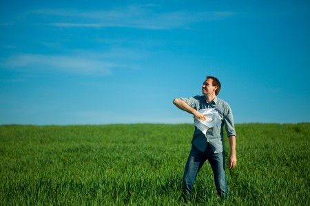 young man throwing a paper in the green field Stock Photo - 7778197