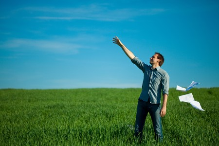 young man throwing a paper in the green field Stock Photo - 7778193