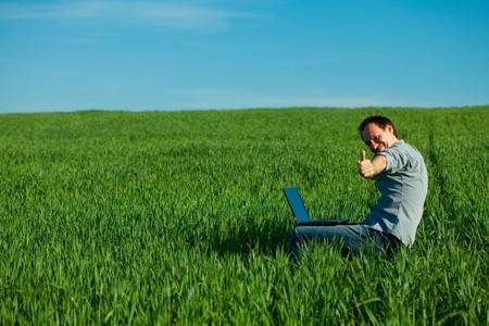 junger Mann mit Laptop im Feld