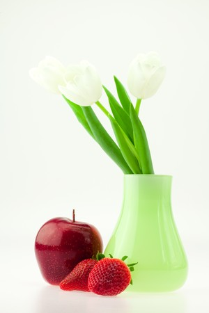white tulips in a vase  apple and strawberry isolated on white photo
