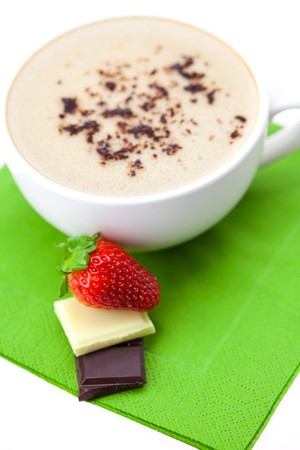 cappuccino cup strawberries and chocolate chips on a green cloth photo