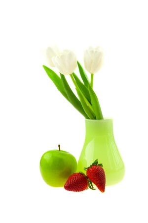 vase with tulips apple and strawberry isolated on white photo