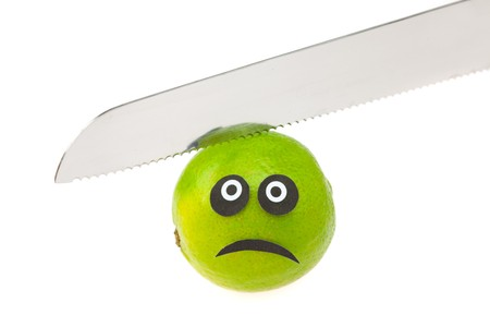 lime with eyes and faces and knife isolated on white photo