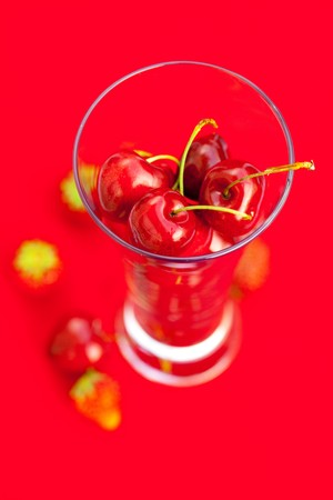 glass of cherry and strawberry on a red background photo