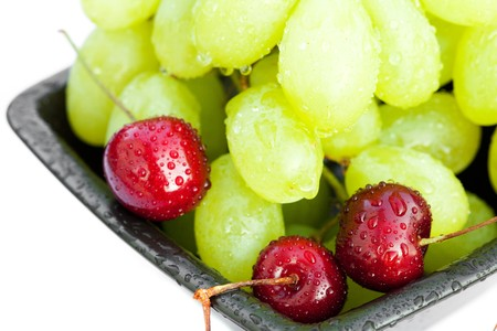 grapes cherry in the bowl is isolated on white photo