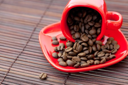 red cup with coffee beans on a bamboo mat photo