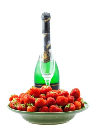 bottle of champagne, wine glass, a plate of strawberries isolated on white photo