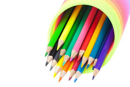 Colorful toy spring and colored pencils isolated on white photo