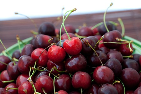cherry in plate on a bamboo mat photo