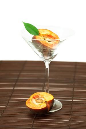 peach in the martini glass on a bamboo mat photo