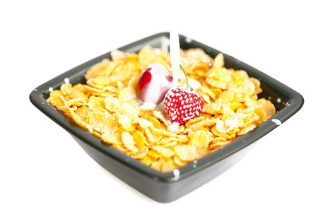 strawberries and cherries in the bowl of Cornflakes with milk isolated on white photo
