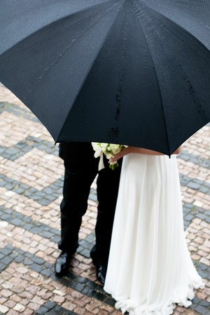 the bride and groom with a bouquet of flowers under the umbrella Stock Photo