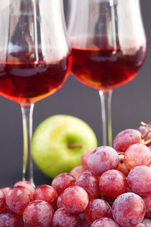 a glass of wine, apple and grape on a black background photo
