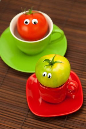 tomato with eyes in the cup on a bamboo mat photo