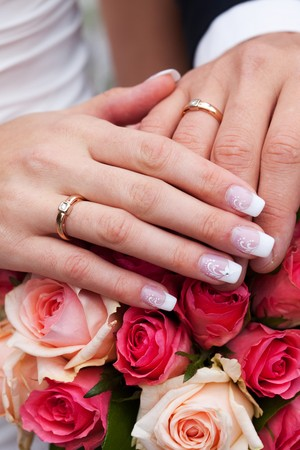 hands of the bride and groom with the rings lying on the bouquet Stockfoto