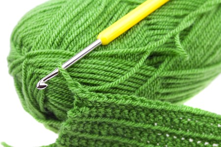 Skein of wool, crochet hook  and knitted piece isolated on white photo