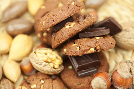 oatmeal cookies, chocolate and nuts on a wicker mat Stock Photo - 8230299