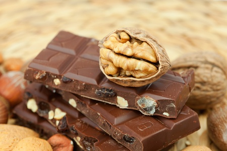bar of chocolate and nuts on a wicker mat photo