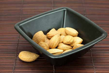 almonds in a bowl on a bamboo mat photo