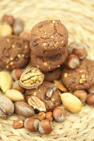 oatmeal cookies, chocolate and nuts on a wicker mat Stock Photo - 8230594