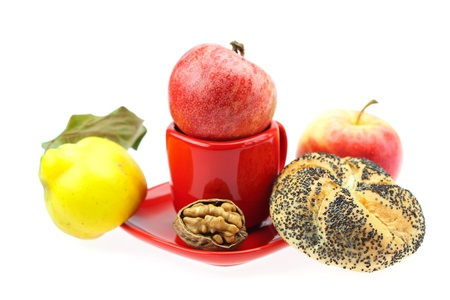 loaf with poppy seeds, quince, apples and walnuts in a cup and saucer isolated on white photo
