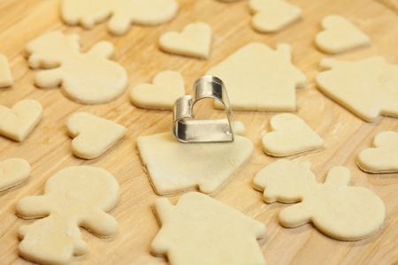 cut dough snowman, house, heart, and forms for cookies photo