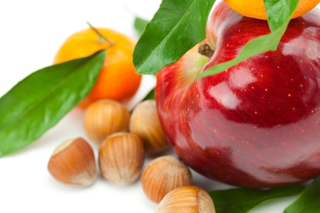 red apple, mandarin  with green leaves and nuts  isolated on white photo