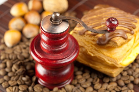 coffee grinder,  cake with chocolate, nuts and coffee beans on a bamboo mat photo