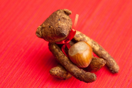 Teddy bear handmade and nuts on a red background photo