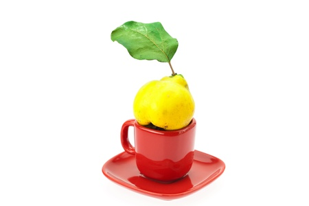 yellow quinces with green leaves in a cup isolated on white photo