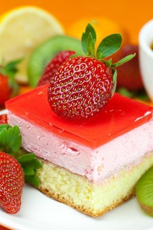 lemon tea, kiwi,cake and strawberries lying on the orange fabric photo